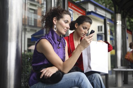 Two young latin women talking at a bus stop, after shopping. photo