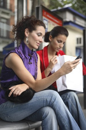 Two young latin women talking  at a bus stop after shopping. Stock Photo