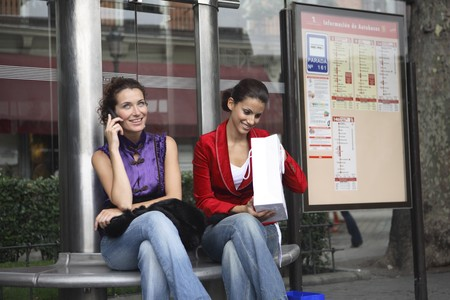 Two young latin women talking on the phone at a bus stop. Stock Photo