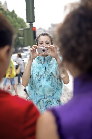 designer labels: One young latin woman taking picture of her friends at Madrid, Spain
