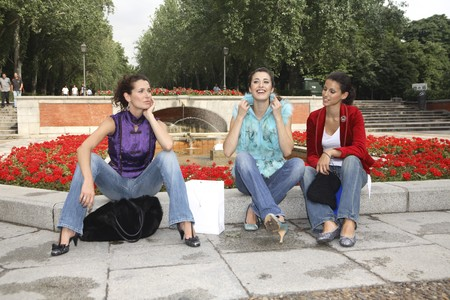 designer labels: Three young latin women resting at the entrance of Park Retiro in front of Puerta de Alcalá, Madrid, Spain