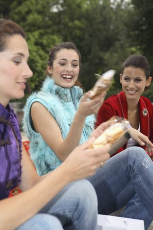Three young latin women resting and talking. photo