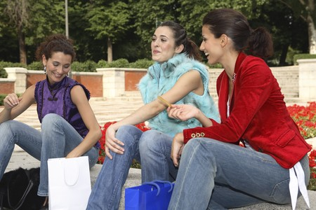 designer labels: Three young latin women resting and talking. Stock Photo