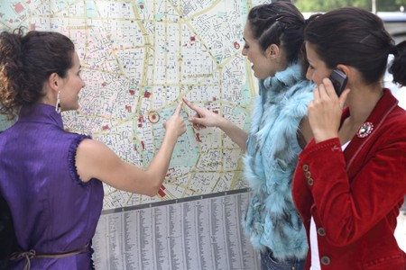 designer labels: Three young latin women talking and looking to a map of Madrid, Spain Stock Photo