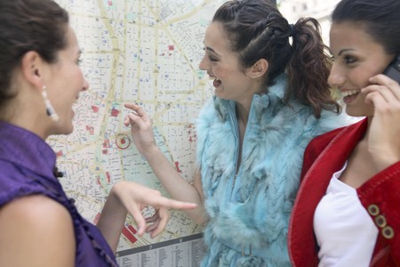 navigation aid: Three young latin women talking and looking to a map of Madrid, Spain Stock Photo