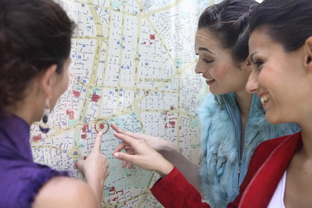 Three young latin women talking and looking to a map of Madrid, Spain photo