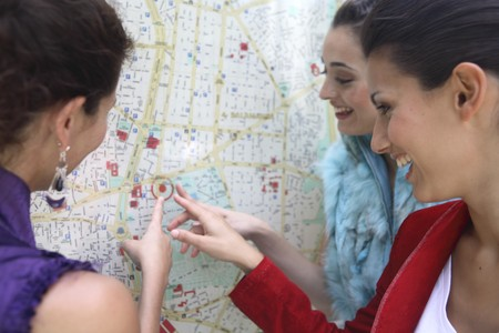 streetlife: Three young latin women talking and looking to a map of Madrid, Spain Stock Photo