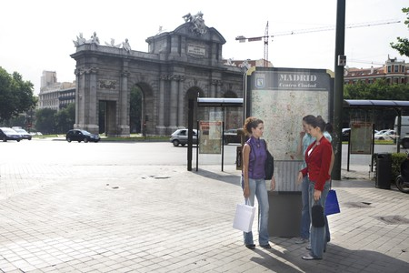 Three young latin women talking and looking to a map of Madrid, in front of at Madrid, Spain photo