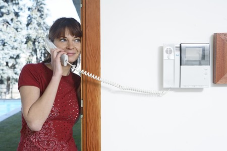 Young woman answering the entryphone from her kitchen