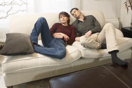 Couple resting on a sofa at home. photo