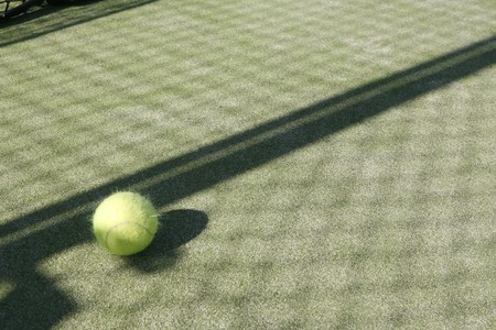 Tennis ball on artificial paddle tennis court.