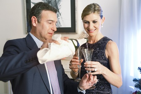 Elegant couple pouring champaign in a glass. photo