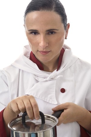 Latin Looking Woman cook dressed in white testing the food. photo