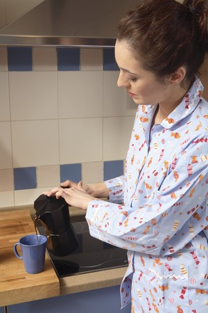 Young woman in pyjama preparing a cup of coffee. Stock Photo - 7475869