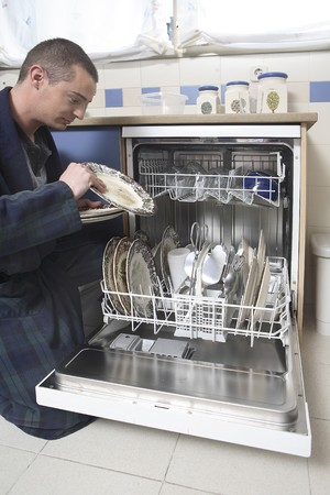 Young man in pyjama placing dishes in the dishwasher. photo