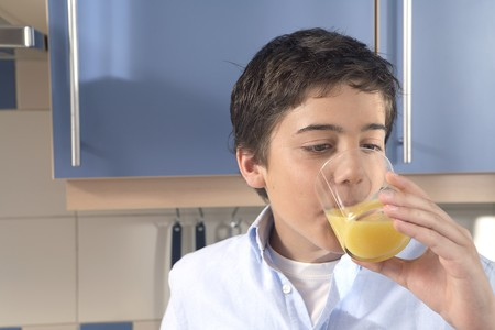 12-15 years old boy drinking a glass of orange Stock Photo - 7475802
