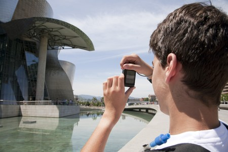 Tourist, 15-year-old young boy, doing photos to the museum Guggenheim, Bilbao, Spain Stock Photo