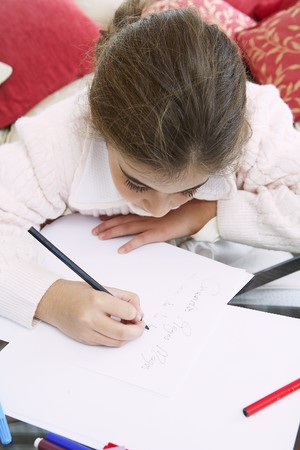 kids writing: Small girl writing the letter to the three magicians. Stock Photo