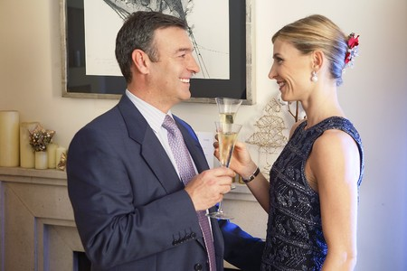 Couple dressed up drinking a toast with champagne.