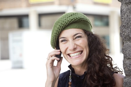 designer labels: Happy and smiling young latin woman talking on the mobile phone. LANG_EVOIMAGES