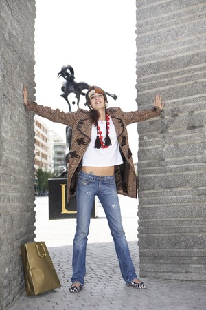 designer bag: Young woman latin model possing with arms open in Avenue Felipe II, Madrid, Spain LANG_EVOIMAGES