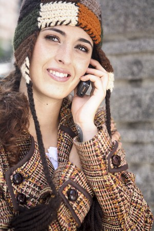 creative industries: Happy and smiling young latin woman talking on the mobile phone. LANG_EVOIMAGES