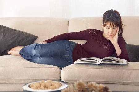 home comforts: Young woman stretched on the sofa, reading a magazine.