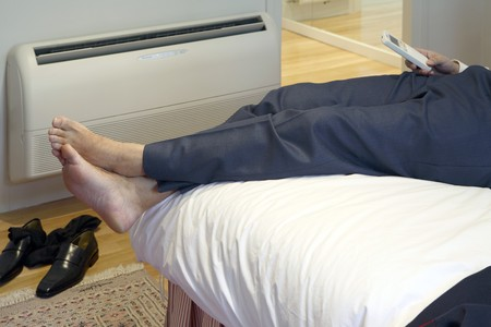 con man: Detail of a adult resting and adjusting the air conditioned in the Hotel room LANG_EVOIMAGES