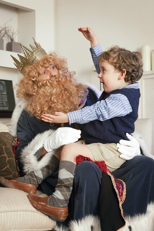 Little boy on top of knees of Magic King. Stock Photo - 7483195
