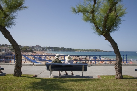 two people with others: Couple resting in a bank in front of the beaches of Santander, Spain