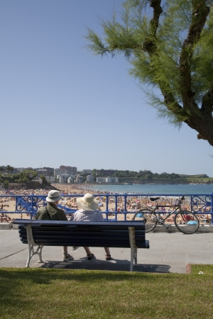 places of interest: Couple resting in a bank in front of the beaches of Santander Editorial