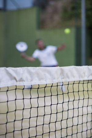 racquetball: Hombre adulto jugando Paddle detr�s de la red.
