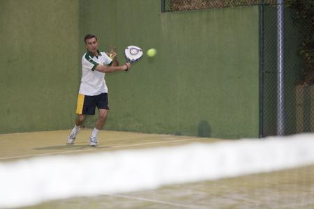 paddle: Adult man playing Paddle behind the net. Stock Photo
