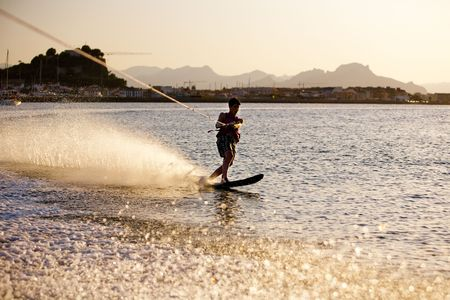 Teenager water skiing at sunset, Denia, Spain