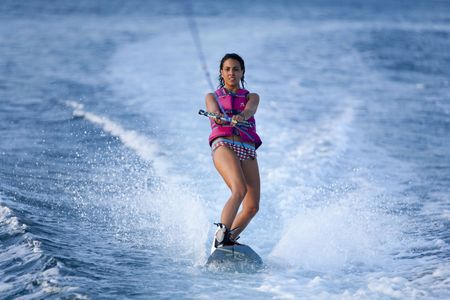 water skiing: Female teenager wake boarding