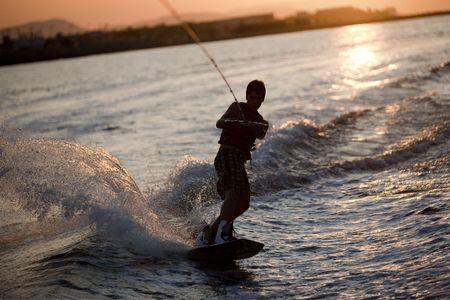 Teenager wake boarding at sunset, Denia, Spain