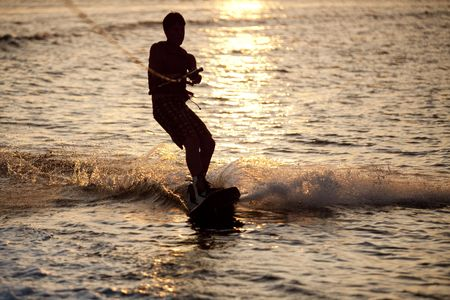 Teenager wake boarding at sunset, Denia, Spain