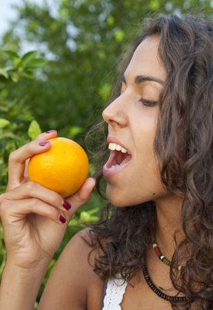 Young Latin Woman eating orange directly from the tree, Valencia, Spain Stock Photo - 7824731