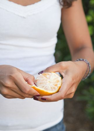 Young Latin Woman peeling orange directly from the tree, Valencia, Spain Stock Photo - 7824727