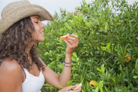adriana: Young Latin Woman eating orange directly from the tree, Valencia, Spain Stock Photo