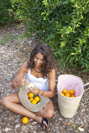 pealing: Young Latin Woman pealing her basket with oranges from Valencia, Spain
