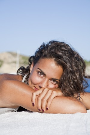 Pretty young latin woman, relaxed sunbathing, looking at camera. photo