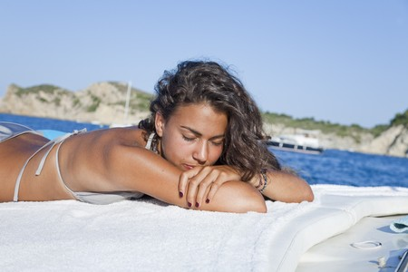 Pretty young latin woman, relaxed sunbathing on boat. photo