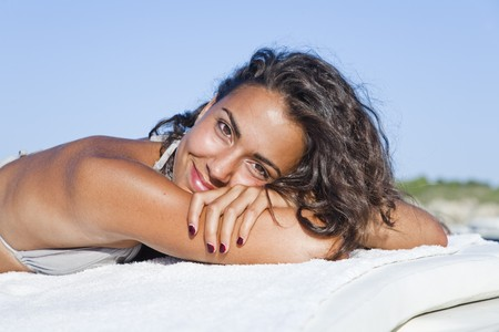 sun bathers: Pretty young latin woman, relaxed sunbathing, looking at camera.