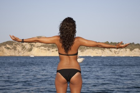 19's: Young woman at the bow of yatch wearing bikini with open arms .