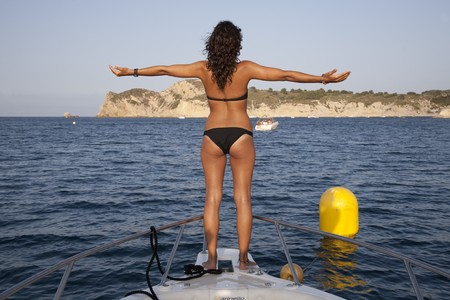 sun bathers: Young woman at the bow of yatch wearing bikini with open arms .