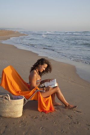 beach wrap: Young pretty woman sunbathing reading a book, at the beach of Valencia , Spain.