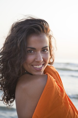 beach wrap: Young pretty woman by the beach, wearing orange sarong. Stock Photo