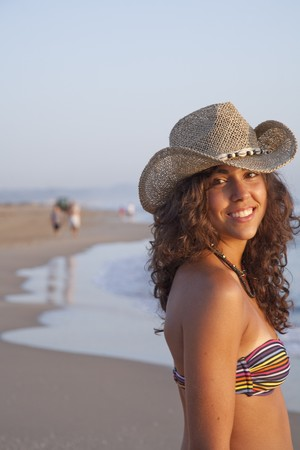 adriana: Young pretty woman by the beach, wearing straw hat.