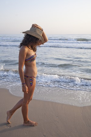 Young pretty woman by the beach, wearing straw hat. Stock Photo - 7908268
